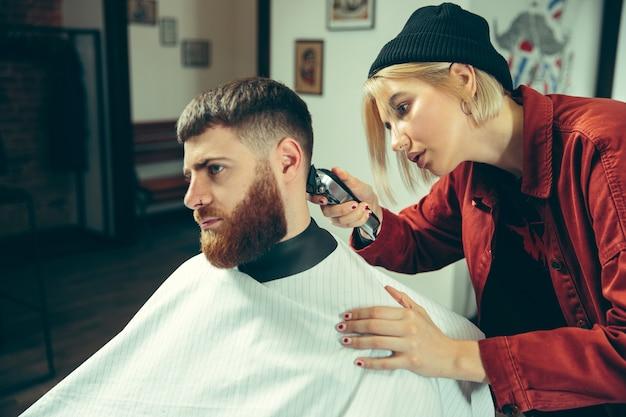 理髪店でひげを剃っている間のクライアント。サロンの女性理髪店。男女平等。男性の職業の女性。