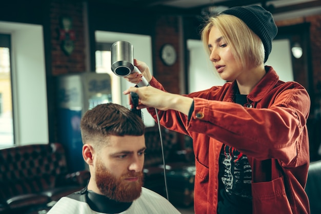 Клиент во время бритья бороды в парикмахерской. женский парикмахер в салоне. гендерное равенство. женщина в мужской профессии.