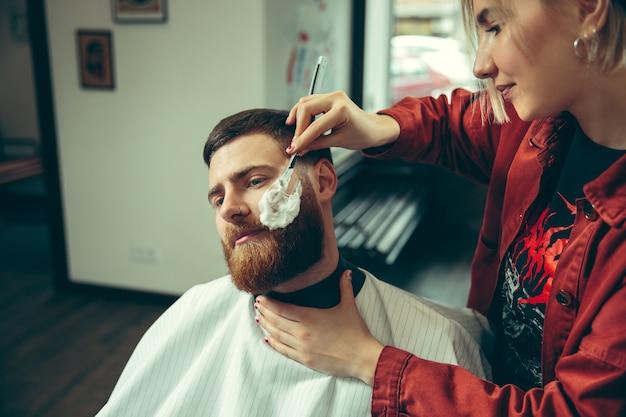Клиент во время бритья бороды в парикмахерской.