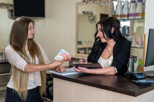 Клиент передает евро администратору салона красоты