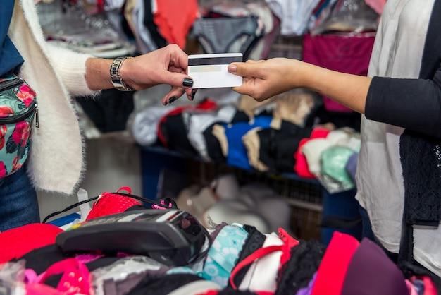 속옷 가게에서 지불을 위해 신용 카드를 제공하는 클라이언트