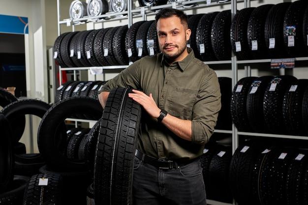 クライアントの男はタイヤのラックごとにタイヤを持って立っています、彼は選択をしました、自動車サービス店で最高のものを買います。肖像画