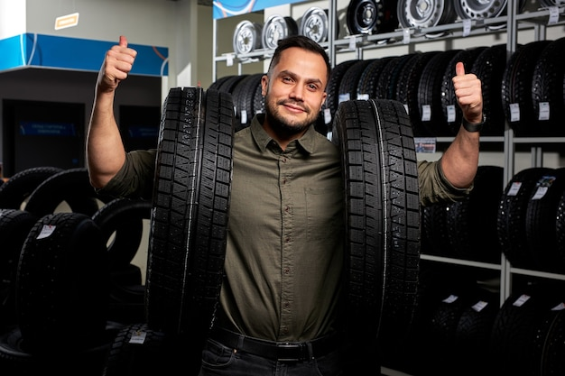 クライアントの男は、タイヤのラックごとに2つのタイヤを持って立っています。彼は選択を行い、自動車サービスショップで最高のタイヤを購入し、カメラに向かって親指を立てて幸せです。肖像画