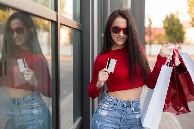 バッグとカードを保持している赤いシャツのクライアント