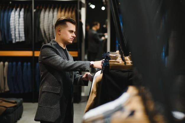 클라이언트는 옷걸이에 걸린 클래식 의상 매장에서 정장 재킷의 가격표를보고있는 우아한 남자입니다.