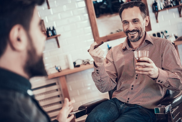 Client is drinking whiskey in a barber shop