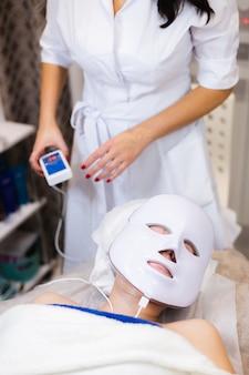 La cliente giace nel salone sul tavolo di cosmetologia con una maschera bianca sul viso