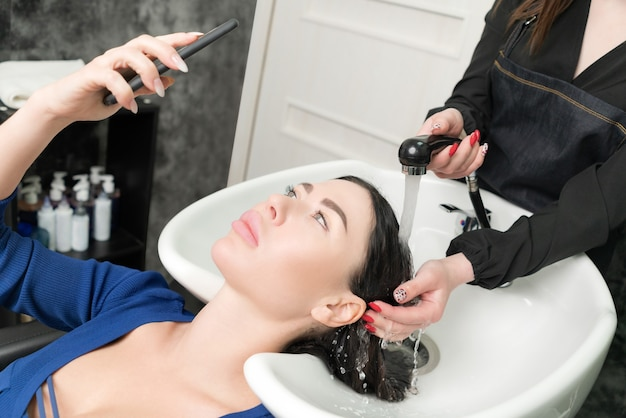 Client looks at phone while hairdresser is busy washing her hair at beauty salon. hairstylist's hands wash long hair of brunette woman with shampoo in professional sink for shampooing in beauty salon.