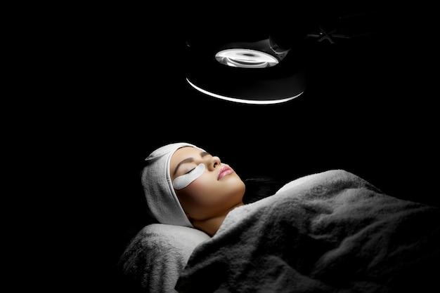 Client lying in cosmetological salon under lamp during lashes enlarging.