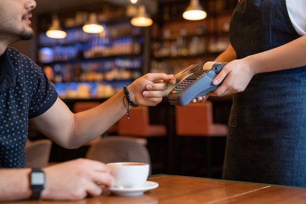現代的なカフェやレストランのクライアントが注文を行い、ウェイトレスに支払いをしている間、支払い機にプラスチックカードをかざします