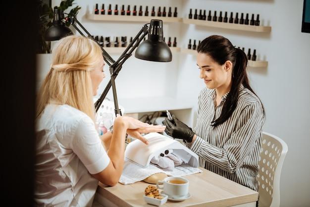 Клиент салона. светловолосая привлекательная клиентка салона красоты общается со своим мастером по маникюру