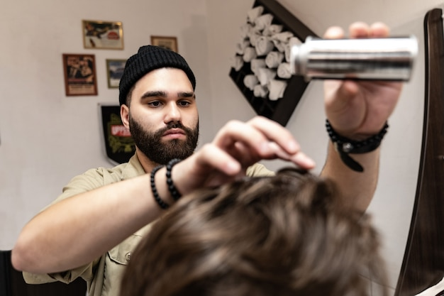 The client receives a haircut and hair styling in a beauty salon. barber serves the client.