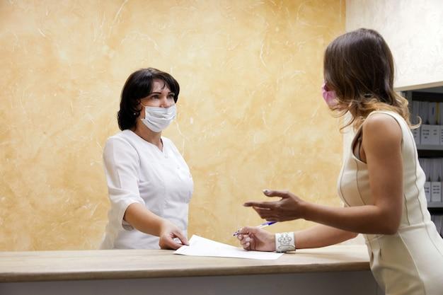 Клиент подписывает бумагу на стойке регистрации в маске для лица