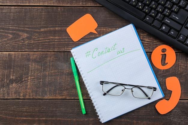 Служба поддержки клиентов. свяжитесь с нами для обратной связи. рабочий стол с блокнотом и очками и различными значками обратной связи. вид сверху