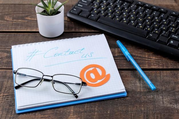 Служба поддержки клиентов. свяжитесь с нами для обратной связи. рабочий стол с блокнотом и очками и различными значками обратной связи.