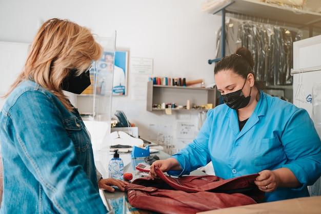 고객이 얼룩이 묻은 옷을 세탁소에 가져가 전문가가 청소합니다.