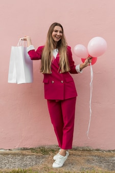Client wearing fashion clothes and holding balloons