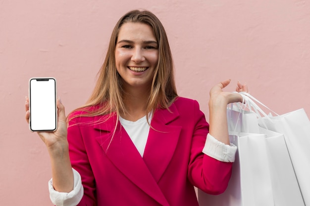 Client wearing fashion clothes and holding mobile phone front view