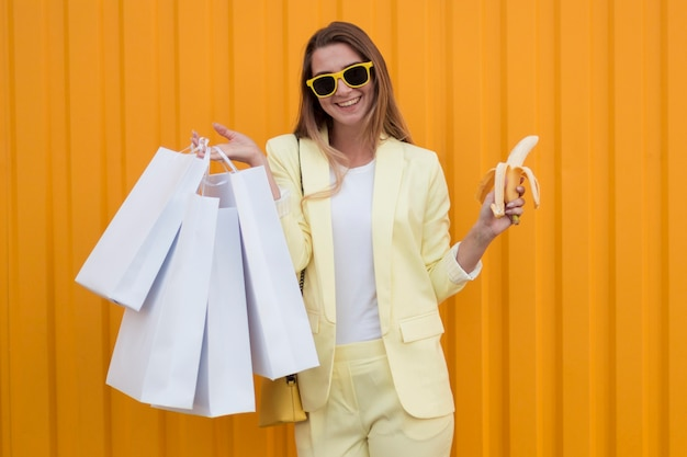 Client wearing yellow clothes and holding a peeled banana