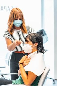 完全な散髪で美容院でマスクを持つクライアント。 covid-19パンデミックにおける美容院の安全対策。新しい正常、コロナウイルス、社会的距離