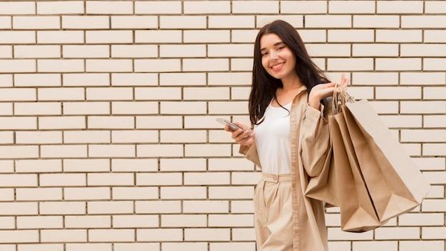 コピースペースのレンガの壁の前に買い物袋を持つクライアント