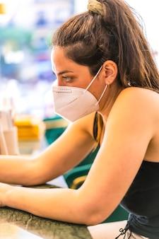 Клиент женщина с маской в лечении ногтей. повторное открытие после пандемии corod-19. салон маникюра и педикюра. коронавирус