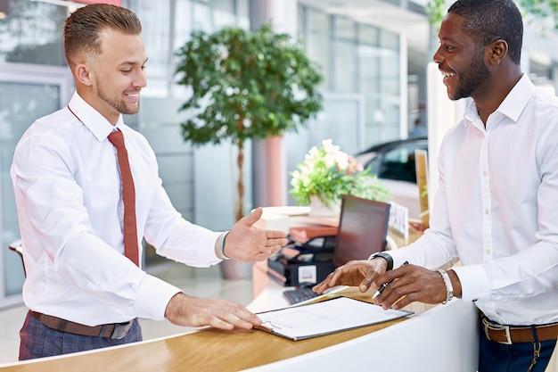 고객과 자신감있는 백인 관리자 또는 컨설턴트가 자동차 쇼룸에서 이야기하고 있습니다.