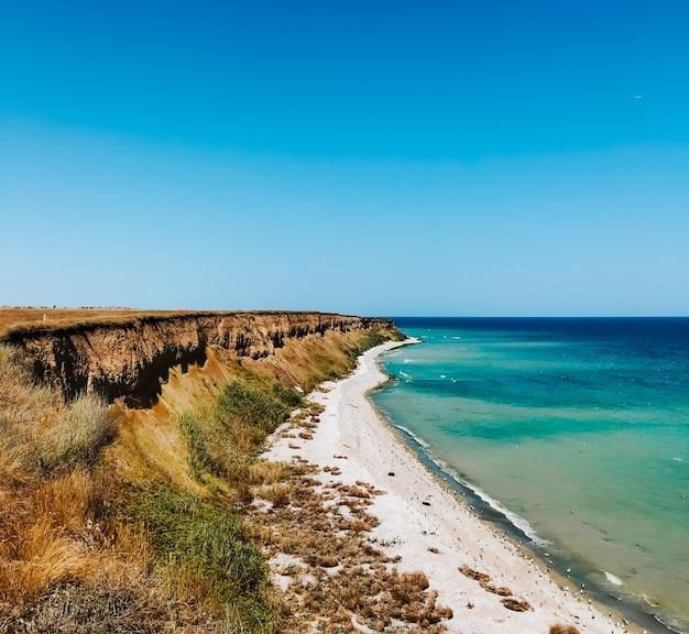 崖の海の青いアクアマリンの波が太陽が降り注ぐビーチに並んでいます。海の泡の柔らかい波。自然な背景の空