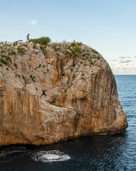 Cliff next to a sea with people jumping in it