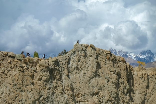 A cliff with snow capped mountains in karakoram range in nagar.