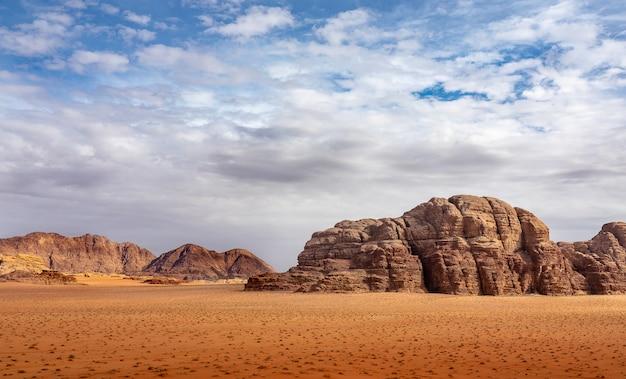 낮에는 흐린 하늘 아래 마른 풀이 가득한 사막의 절벽과 동굴