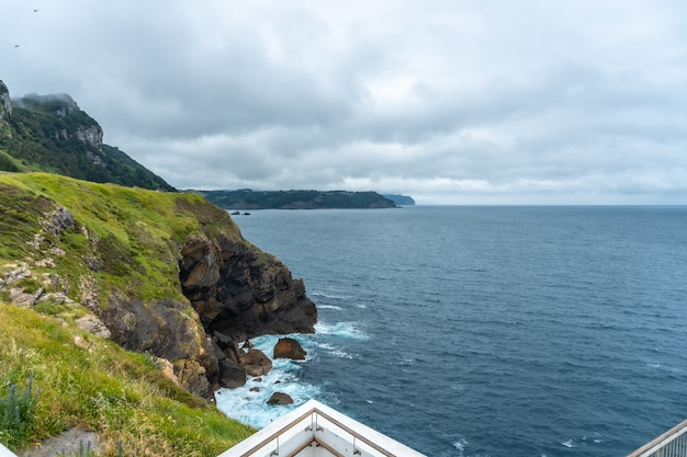 Cliffs next to the santa catalina de lekeitio lighthouse on a cloudy spring morning, with the sea in the background, landscapes of bizkaia