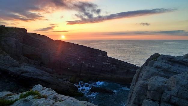 日没時に日光の下で海に囲まれた崖