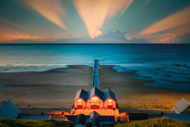 Вид с утеса на пирс на закате солтберна у моря, северный йоркшир, великобритания