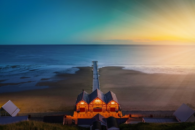 Clifftop view of pier at twilight time of saltburn
