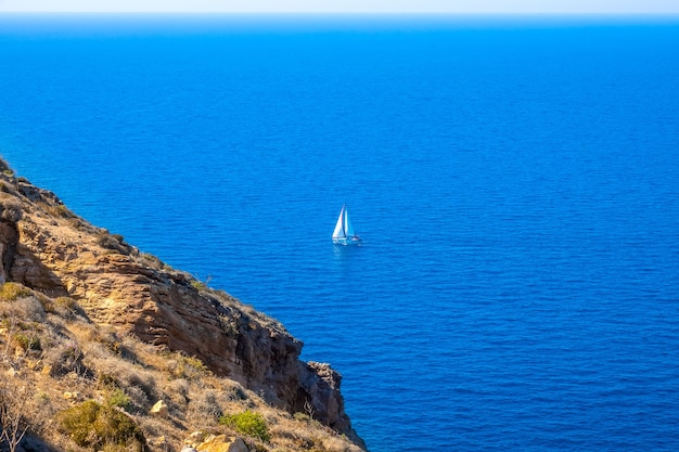 青い海の崖の海岸とセーリングヨット