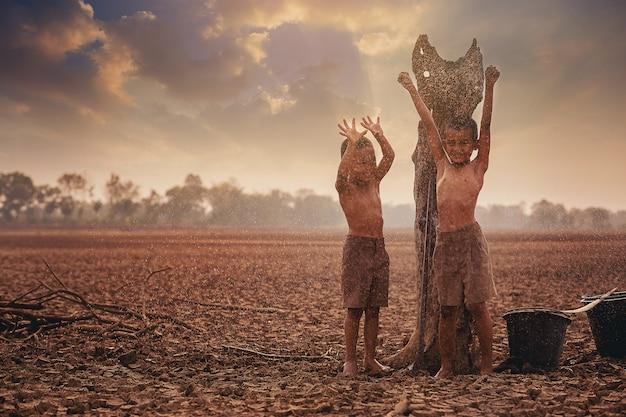 気候変動アジアの少年たちは、乾燥したひびの入った土地で最初の降る雨季を楽しんでいます環境保全と地球温暖化の概念の停止