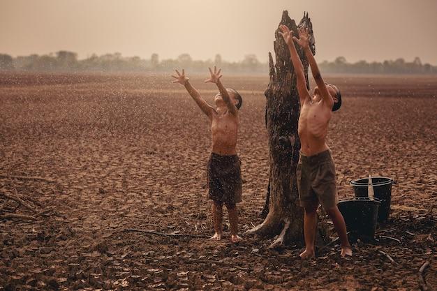 기후 변화 아시아 소년은 마른 갈라진 땅에 첫 번째 내리는 우기를 즐기고 환경 보전 및 지구 온난화 개념을 중지
