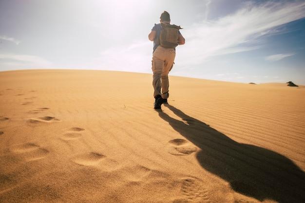 Концепция изменения климата с человеком, идущим с рюкзаком в засушливой песчаной пустыне под теплым солнцем и без воды - опасность для будущего планеты - концепция дикой природы