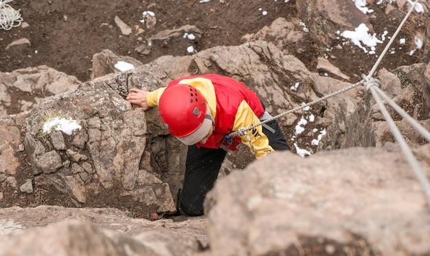 岩を登るクライマーの大人の女性。冬の季節。上面図