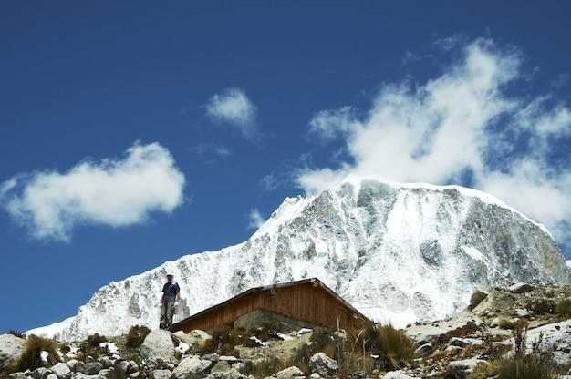 Альпинист, хижина и пик ранрапалка в кордильерах
