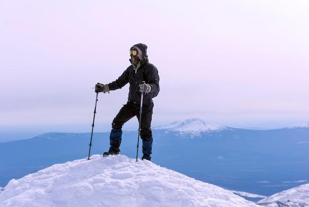 防風マスクと眼鏡をかけた登山家が山の雪の頂上に達した