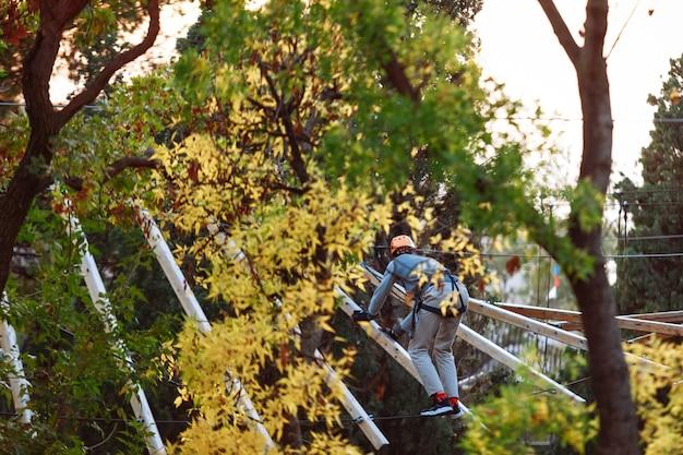 薄手の木製のバーの上を歩くための機器列車の登山者