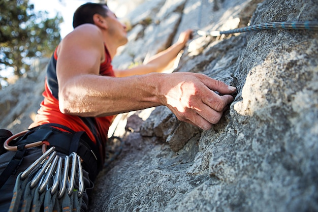 Climber in red t-shirt climbs a gray rock