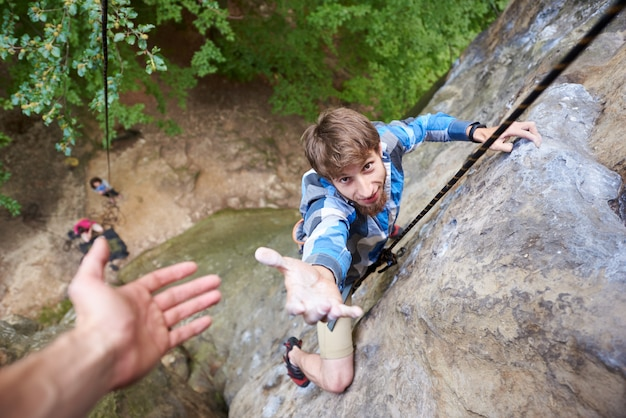 Climber rock climbing overhanging cliff with rope. asking for help. man helping his friend to climb a rock.