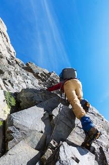 岩だらけの地形でスクランブリングする登山者
