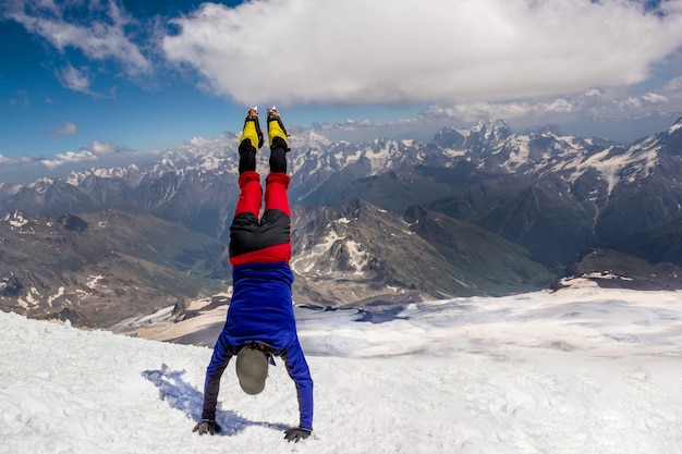 Climber standing upside down on his hands on top of the mountain