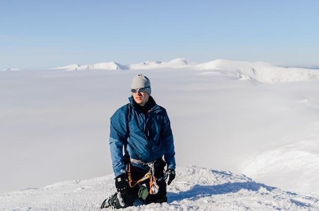 Альпинист с оборудованием на вершине горы