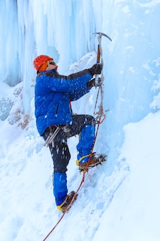 Climber with ice axe storms the vertical wall of the glacier