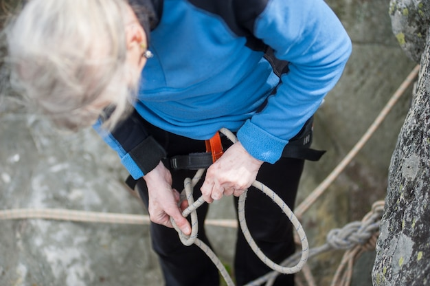 Climber woman in safety harness tying rope in bowline knot